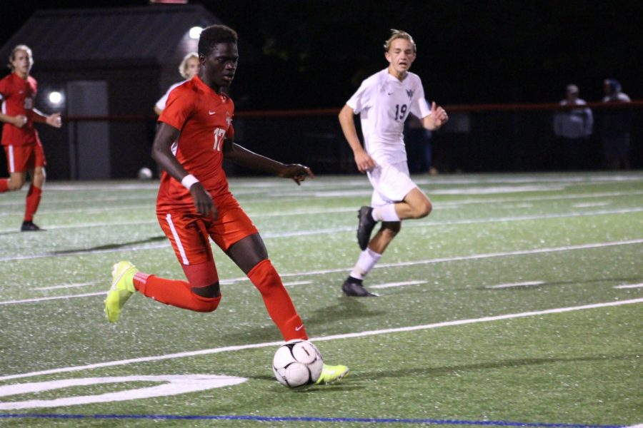 Sophomore Fallou Cisse drives the ball downfield during a home game against West York on Sep. 19. Photograph by Maggie Grim