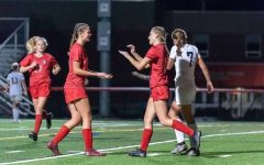 Girls Soccer Varsity Players celebrating during a game.  Photograph by Tim Flaherty