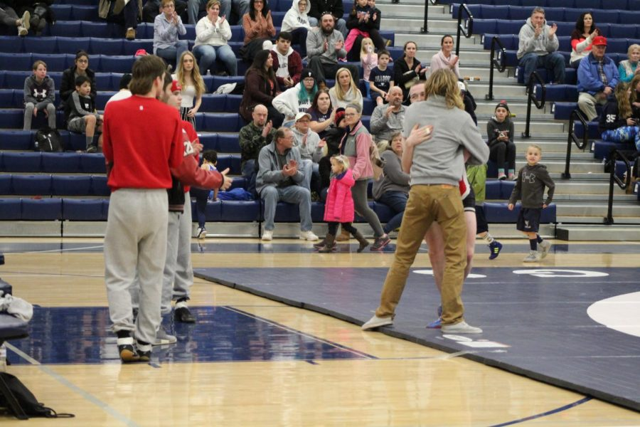 """Head coach Aaron Trimpey congratulates Romjue after he makes his way off of the mat. """"We are beyond proud of him and I am glad I could be a small part of it,"""