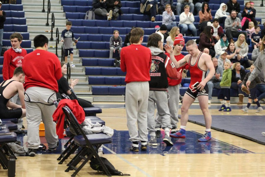 The team congratulates Romjue after he makes way toward the assistant coach. Romjue is one of four wrestlers who have accomplished the 100 wins. Last wrestler to make this accomplishment was Adam Loppiccolo in 2003. Photograph by Mackenzie Womack.