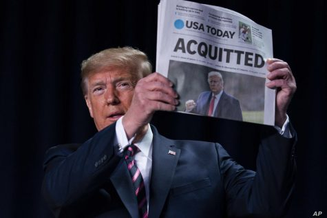 Donald Trump shows the newspaper edition of his acquittal on the impeachment trial. Photo courtesy Voice of America via voiceofamerica.com