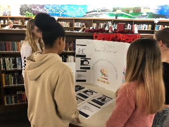 Freshmen, Olivia Mcglaughlin and Sydney Brown look at Peyton Savage and Emily Goodfellow's project on sexual assault. Photograph by KC O'Neill