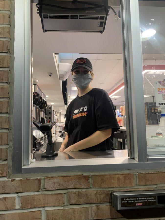 Claire Miller runs the drive thru at Dunkin Donuts. Photograph by: Julianna Kessler