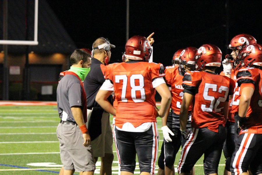 Wiles and assistant coach Joe Sorice talk to players during a stoppage of play in the closing minutes of the game. Susquehannock lost the game 36-10. Photograph by KC O'Neill