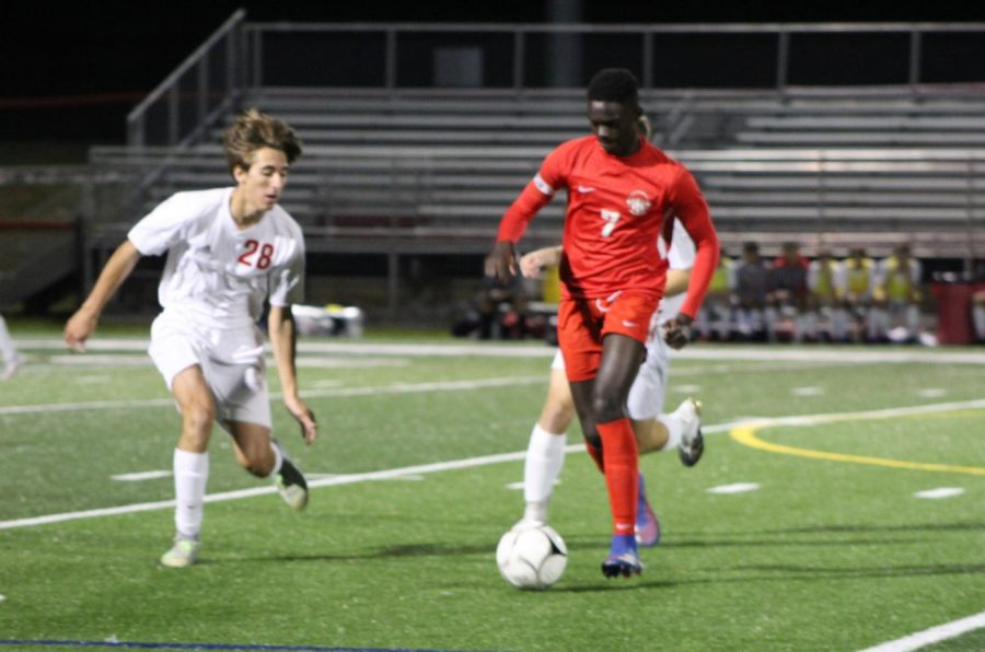 Fallou Cisse dribbles the ball down the field against the opposing team. Photograph by Maggie Grim.
