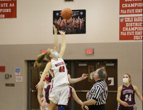 "Senior Kaelyn Duvall takes the jump ball to Start the game. ""I would say the toughest part of doing a jump ball is getting the timing perfect where I can have the advantage of getting up high enough to push the ball to one of my teammates,"" said Duvall. Photograph by Lola Sroka"