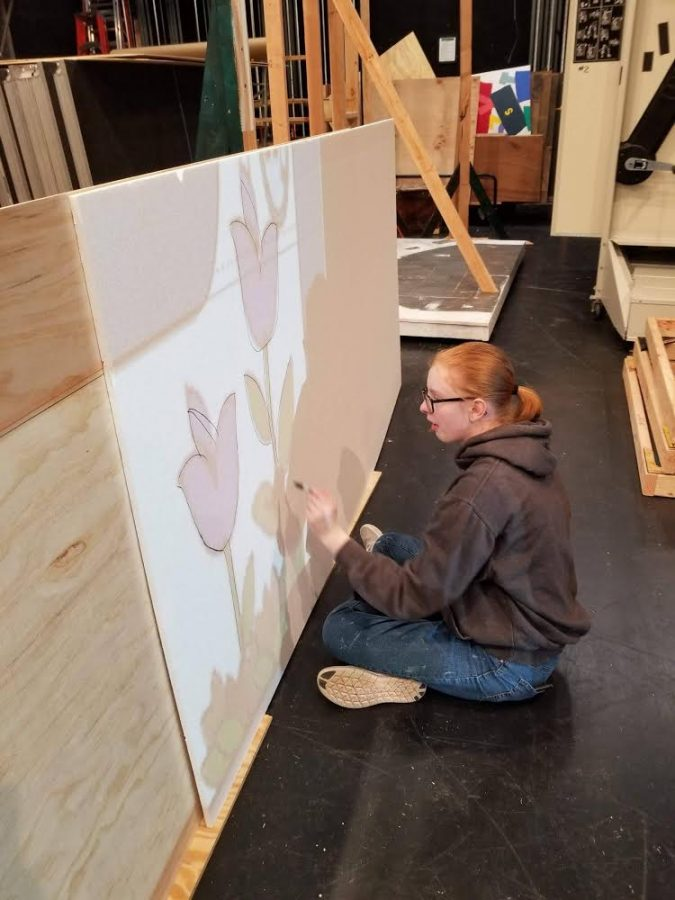 Marusko tracing an image onto a board, in order to create a background for the production. Photo courtesy of Alexandra Marusko.
