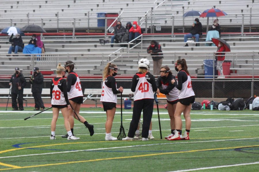 (Left to Right) Seniors Kathryn Burke, Ariana Prediger, Allie Abel, sophomore KC O'Neill, junior Katlyn Krebs and senior Jordyn Prediger huddle up to go over the game plan during a girls lacrosse practice on the stadium field in mid-March. The girls  lacrosse team welcomed new head coach this spring.