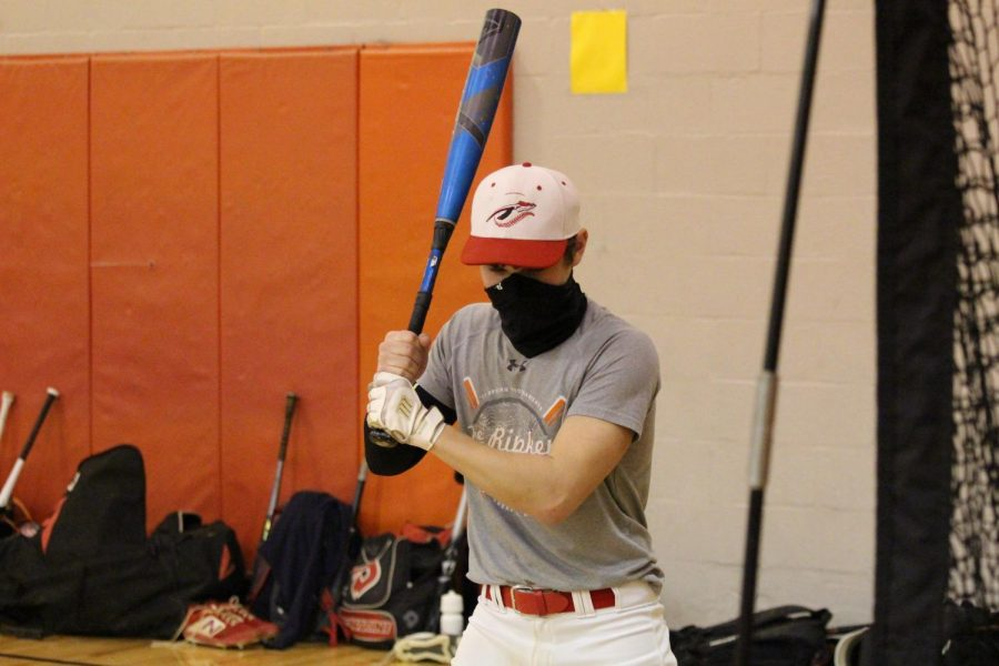 Sophomore Luke Geiple squares up to the plate during a hitting drill at baseball practice. The baseball  program has a new head coach this year in Joel Stoneberg.