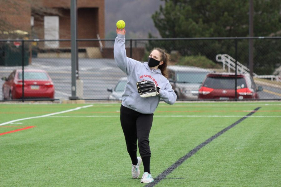 Junior Marissa Mussmacher throws across the field during one of the first varsity softball practices. The softball team often will practice on one of the turf fields because of wet conditions on the softball field.