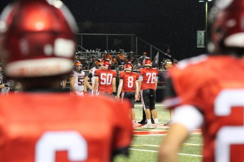 Senior captains Hunter Sturgill (50), Zach Pecunes (8), and Mason Kight (78) stand together for the pregame coin-toss. The Warriors began the game by receiving the ball. Photograph by Mackenzie Womack.