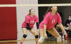 Senior middle hitter Maddie Gajewski stands behind sophomore middle hitter Sydney Wilson after the serve goes over the net. Photograph by Maggie Grim.